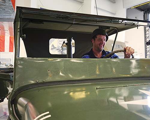 George pretending to drive an Army Jeep